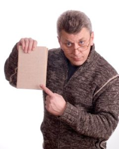 The man in glasses shows a finger on the book on a white background
